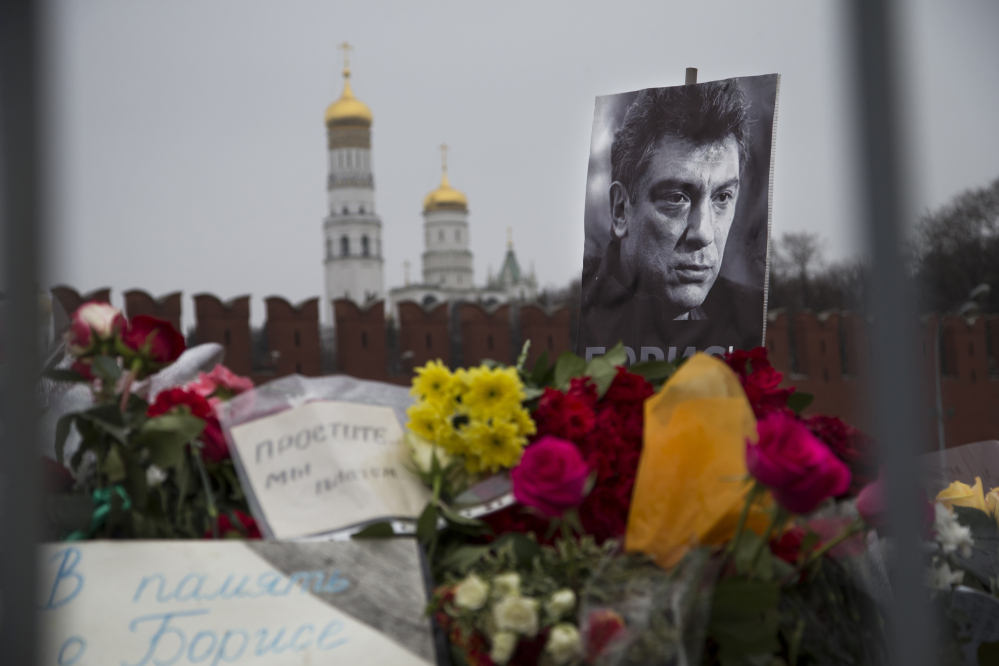"""Flowers and a condolence message that reads """"In memory of Boris"""" are placed with a portrait of Boris Nemtsov, a charismatic Russian opposition leader and sharp critic of President Vladimir Putin, at the site where Nemtsov was gunned down near the Kremlin, against a backdrop of the Kremlin Wall, in Moscow on Monday."""