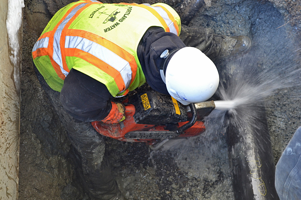 Evan Haines of the Portland Water District cuts a pipe Monday while repairing a water main that ruptured under Stroudwater Street in Westbrook. A section of cast iron pipe was replaced.