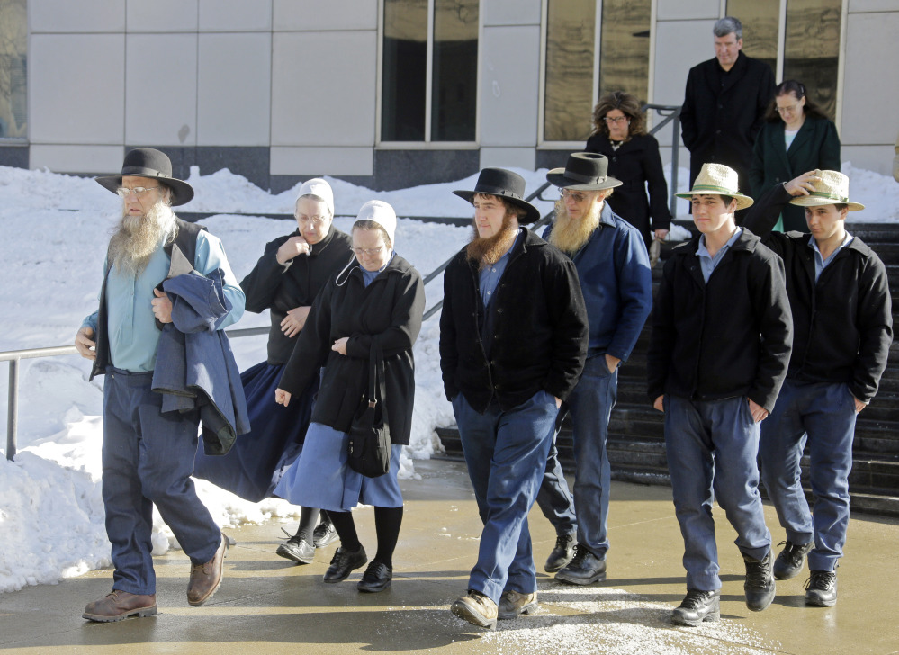 Members of an Amish community in Bergholz, Ohio, leave federal court in Cleveland after a hearing Monday. Sentences were reduced Monday for Sam Mullett, the leader of a breakaway group, and seven of his imprisoned followers who chopped off the hair and beards of Amish people with whom they disagreed.