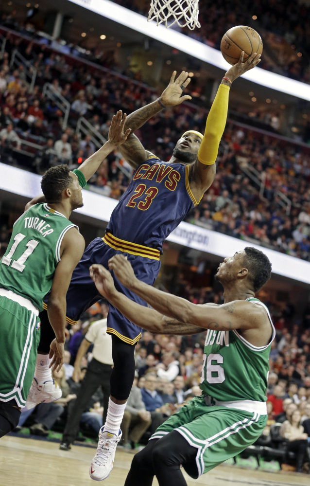 The Cleveland Cavaliers' LeBron James shoots against the Celtics' Evan Turner (11) and Marcus Smart in the first quarter of Tuesday night's game in Cleveland. James scored 27 points in just 26 minutes on the court.