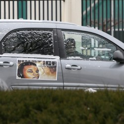 Members of the Brown family, including his mother, Lesley McSpadden, leave the St. Louis FBI offices in a car decorated with Michael Brown's photograph after meeting with federal officials on Wednesday. The Justice Department won't prosecute a former Ferguson, Missouri, police officer in the shooting death of Michael Brown, but has faulted the city and its law enforcement for racial bias and unconstitutional practices.
