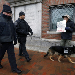 Boston police officers walk past protester Joe Kerbartas outside federal court Wednesday in Boston, on the first day of Boston Marathon bombing suspect Dzhokhar Tsarnaev's federal death penalty trial.