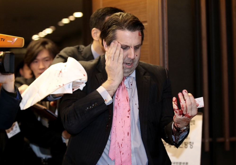U.S. Ambassador to South Korea Mark Lippert leaves a lecture hall for a hospital in Seoul, South Korea, on Thursday after being attacked by a man screaming that the rival Koreas should be unified, South Korean police and media said Thursday