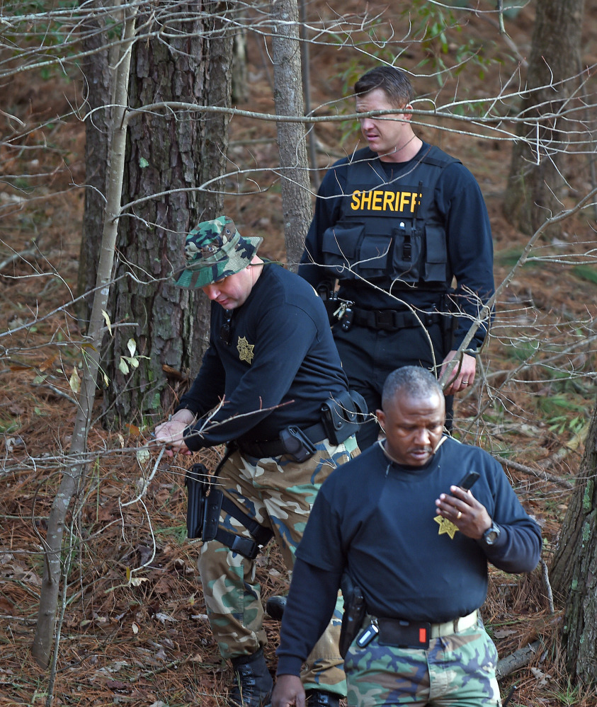 Wilson County sheriff's deputies investigate an area near Interstate 95 Monday in Wilson, N.C., where armed robbers took $4.8 million in gold bars from an armored truck.