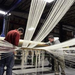 Nick Krueger and Patrick Kirby work in the warping department attaching cotton yarn from creels to a warp beam that will be used on a loom at Brahms Mount in Monmouth.