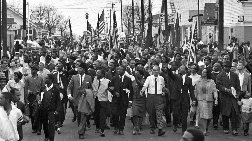 Martin Luther King, foreground row, waves with marchers on March 21, 1965 – an event that put Selma, Ala., on the map of the national conscience.