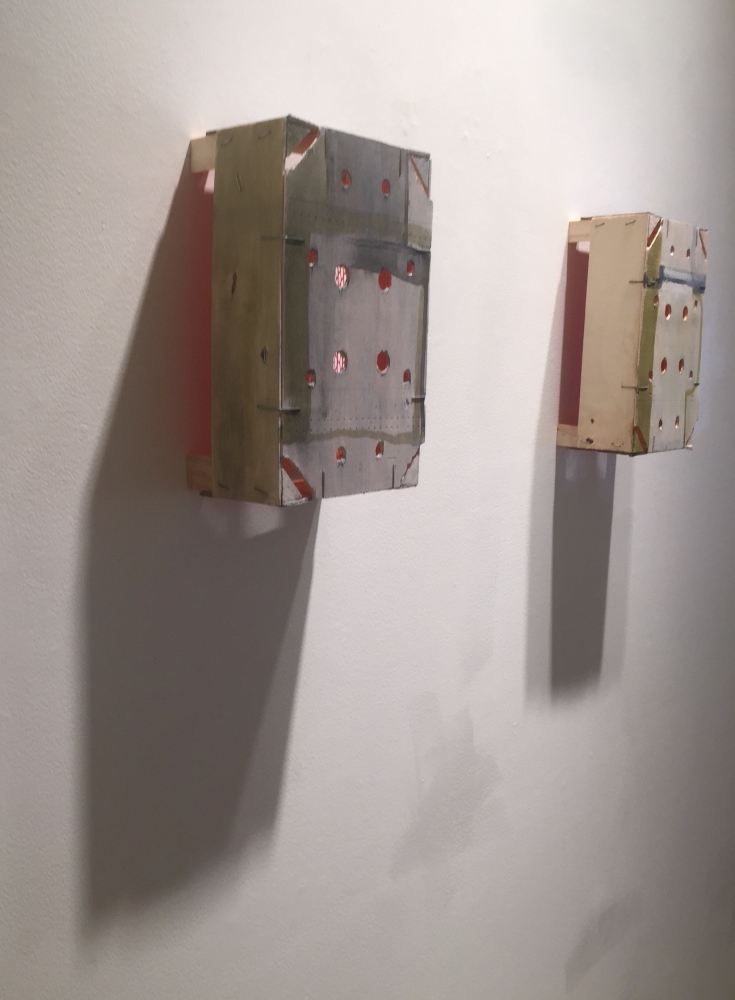 Viewers will see the orange interiors of Lynda Litchfield's painted wooden crates as reflected light on the wall.