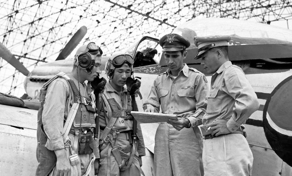 """Lt. Col. Dean Hess, second from right, points out target areas on a map in 1950 as he briefs two American-trained South Korean pilots just before takeoff. Brig. Gen. Kim Chung Yui, chief of staff of the Korean air force, is at right. Rock Hudson played Hess in """"Battle Hymn."""""""