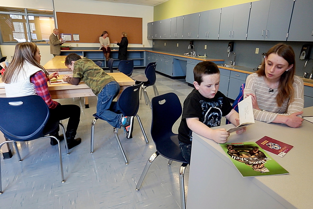 """Megan Brown, 18, right, a volunteer reading mentor in the Teen Trendsetters program, helps Jacob Rice, 6, read a book at Buxton Center Elementary School. """"It's nice when they catch onto something,"""" Brown said. Their success """"makes you really feel good."""""""