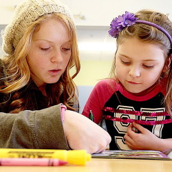 Kialeigh Marston, 17,  left, reads with Bayley Rafuse-Morse at Buxton Center Elementary School. Elementary school students  gain more reading skills and learn to enjoy reading, when Teen Trendsetters volunteers take time to read with them.