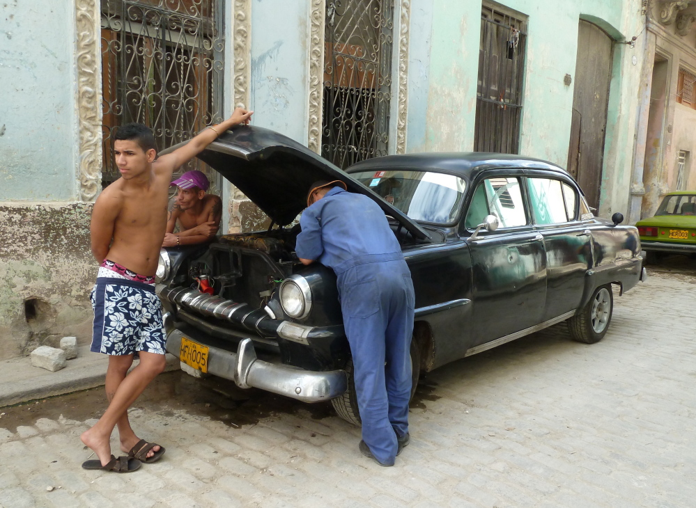 Men work on a car near Adath Israel, the only Orthodox Jewish synagogue remaining in Cuba, in 2013. Cuba has fewer than 1,500 Jews today, although as many as 24,000 lived there in the 1920s, according to various sources.