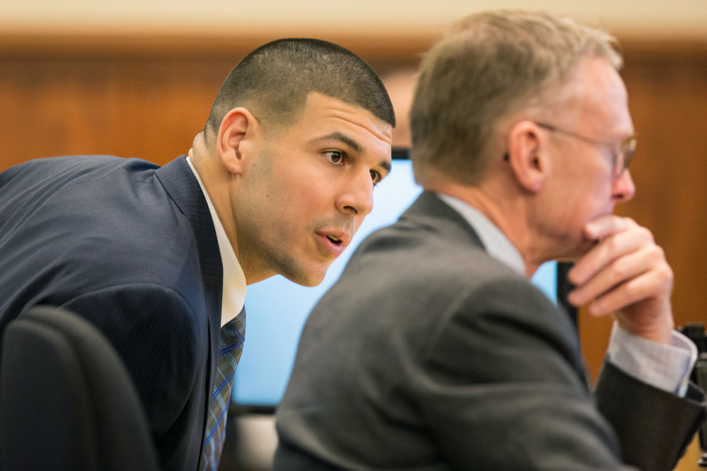 Aaron Hernandez speaks with his attorney Charles Rankin during the murder trial of the former New England Patriots player Monday at Bristol County Superior Court in Fall River, Mass.