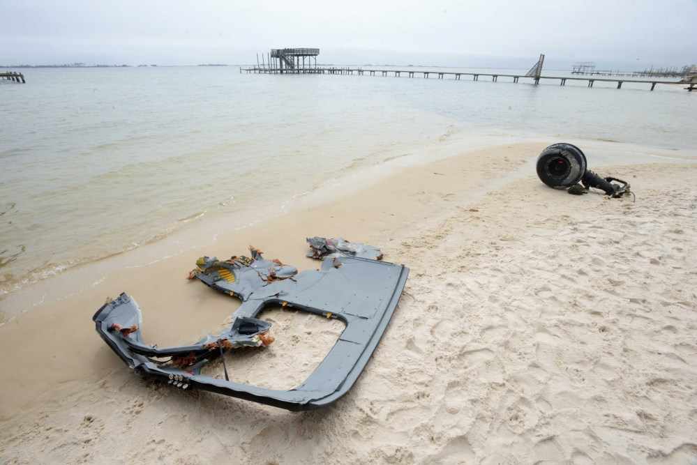 A wheel and pieces of fuselage from an Army Black Hawk helicopter lie along the shoreline of Santa Rosa Sound near Navarre, Fla., on Wednesday. Search and rescue crews combed the water looking for service members who were on the aircraft when it went down in the area Tuesday evening.