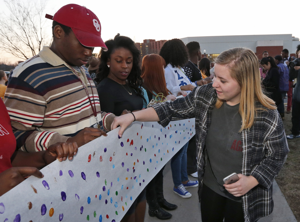 University of Oklahoma junior Brooke Aston, right, of Rockwall, Texas, adds her fingerprint to a sign to be carried to the now-closed University of Oklahoma's Sigma Alpha Epsilon fraternity house during a rally in Norman, Okla., on Tuesday.
