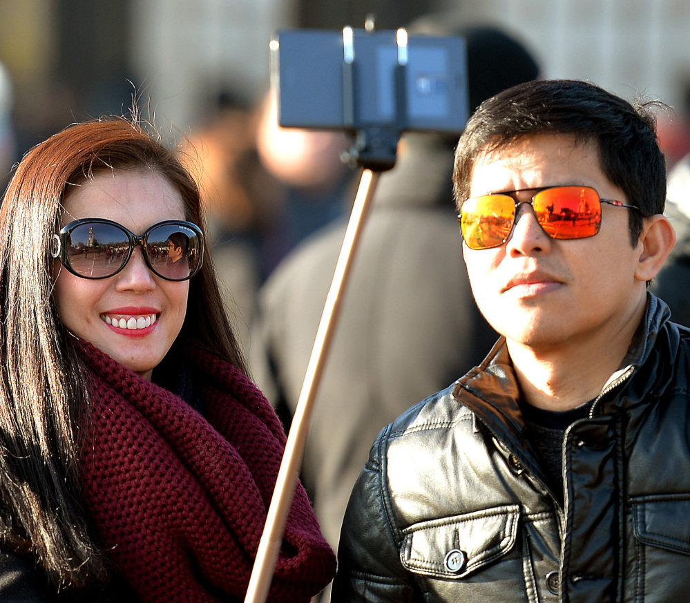"""Tourists use a """"selfie stick"""" in London. A French palace and a British museum have joined the growing list of tourist attractions banning the devices. The Associated Press"""