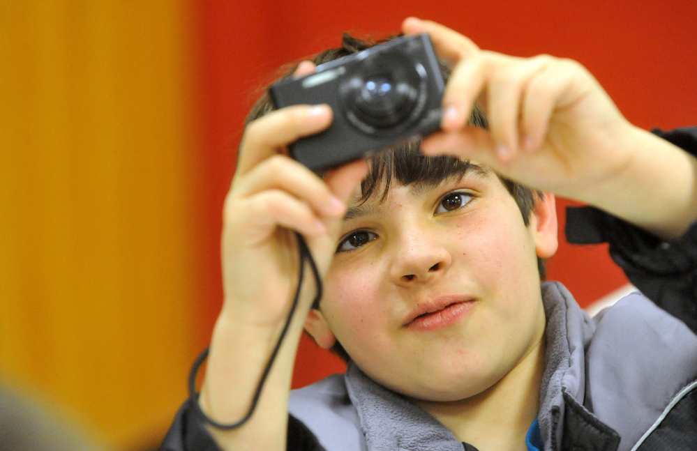 Owen Schuchardt, 11, snaps a photo during a photo club class with photographer Eric Gottesman at the Alfond Youth Center on Wednesday.