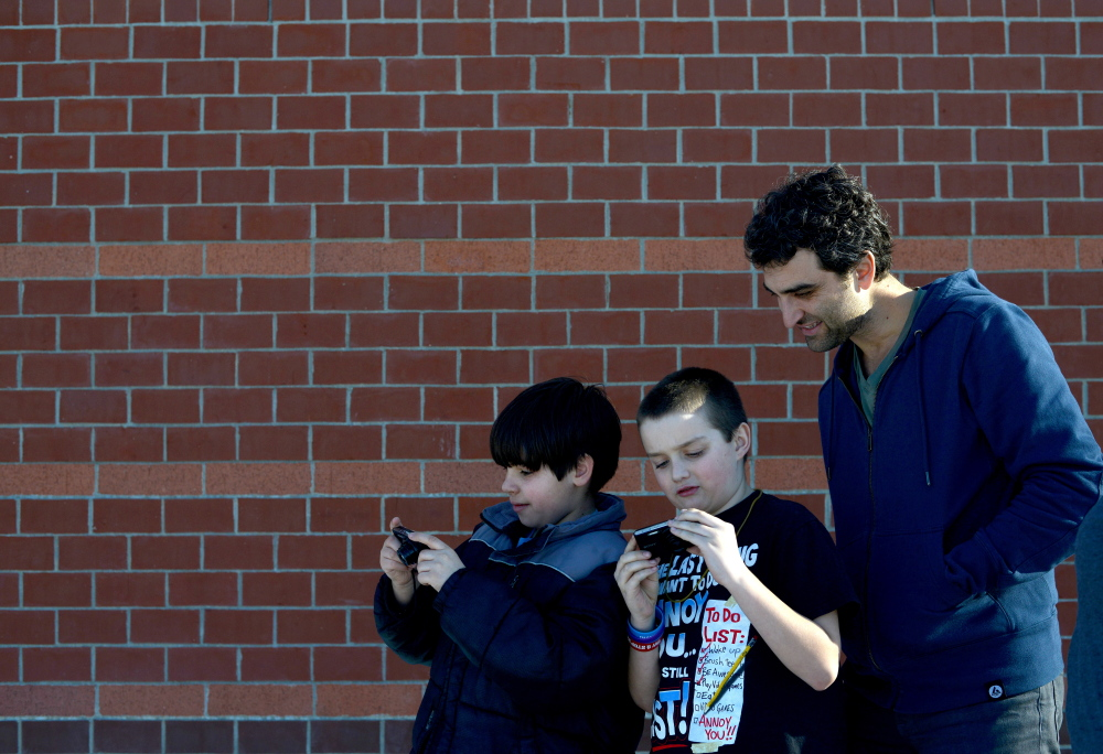 Owen Schuchardt, left, and Jacob Luff, center, share their photos with their photography teacher, Eric Gottesman, during a photo club class at the Alfond Youth Center on Wednesday.