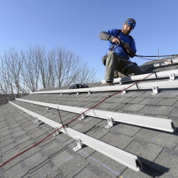 Zach Good of ReVision Energy prepares a roof for solar panels Wednesday at a home on Overlook Lane in Cape Elizabeth. Maine is in the midst of a debate on solar power's role in the state's future.