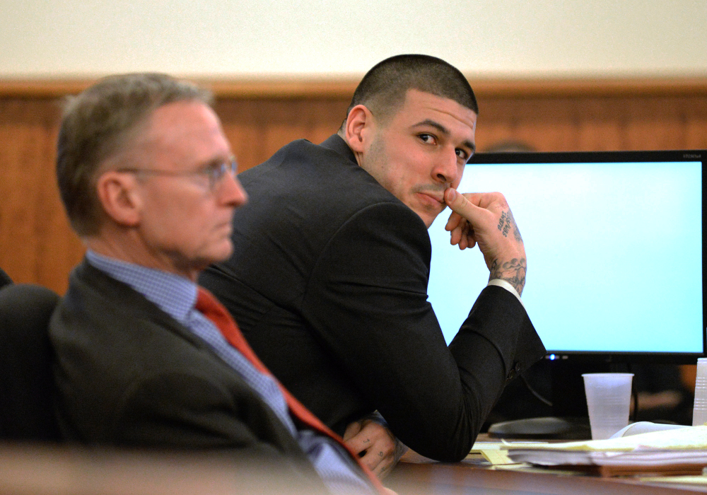 Former New England Patriots football player Aaron Hernandez sits with attorney Charles Rankin, as he tries to refrain from laughing during the testimony of Anthony Jerome, a former W Hotel Valet, during his trial Tuesday at Bristol County Superior Court in Fall River, Mass.