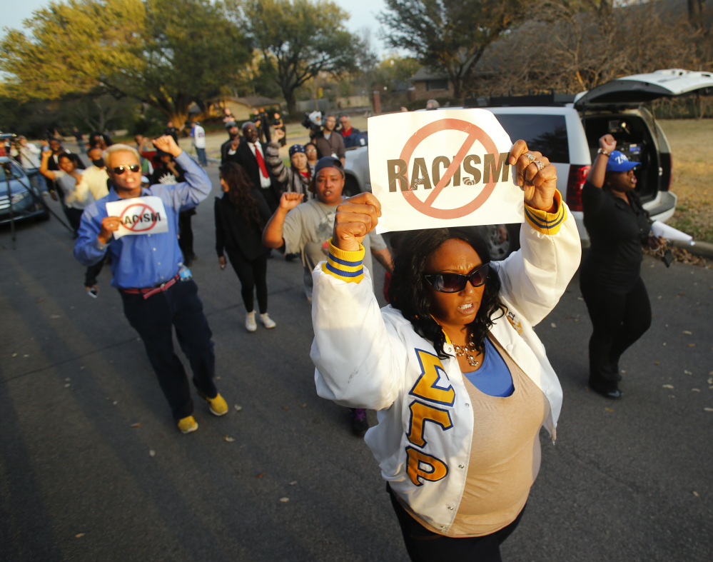 Darmita White holds a sign to protest outside of the home of Parker Rice, a University of Oklahoma student caught on video in a racist fraternity chant, in Dallas on Wednesday.