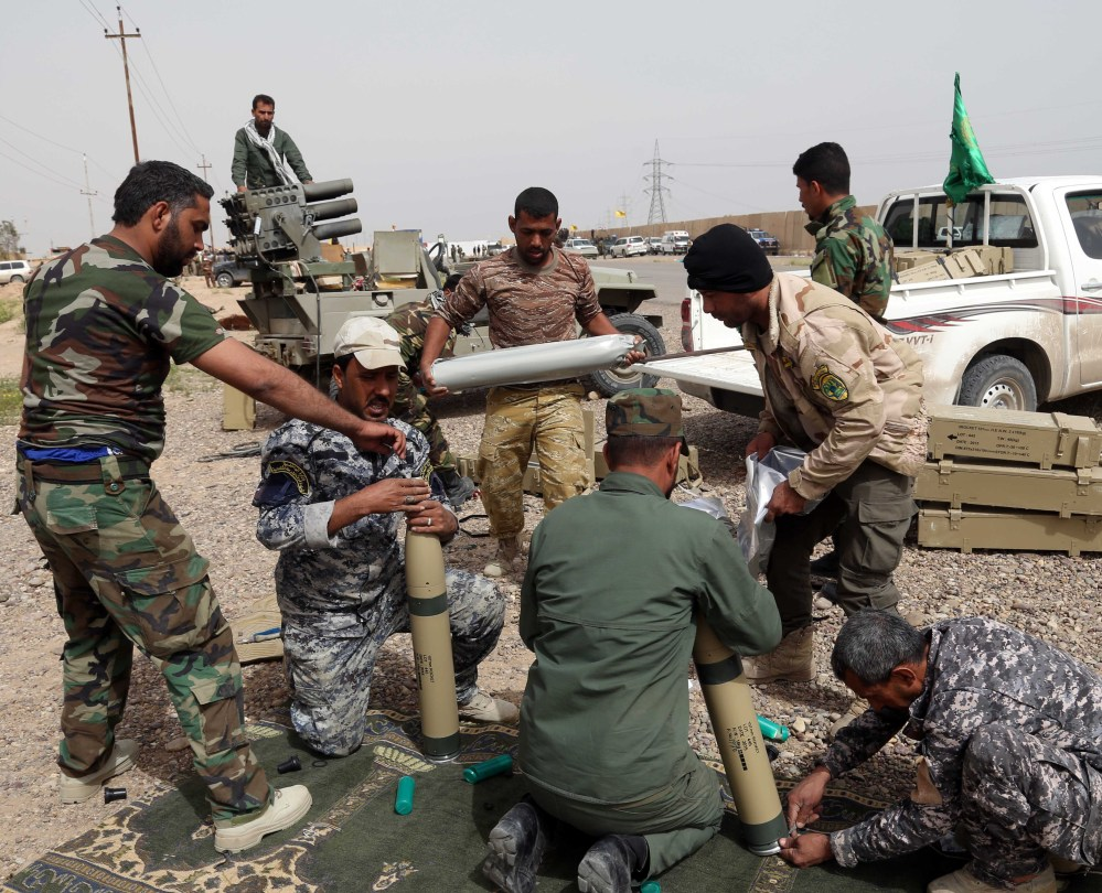 Members of an Iraqi Shiite militant group called Soldiers of Imam Ali Brigades prepare to launch rockets Friday against Islamic State extremists' positions in a neighborhood in Tikrit.