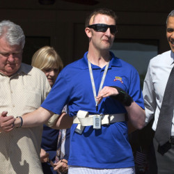 President Obama, right, walks with Army Ranger Sgt. 1st Class Cory Remsburg on Friday. Obama says service at VA hospitals has greatly improved since a scandal last year.