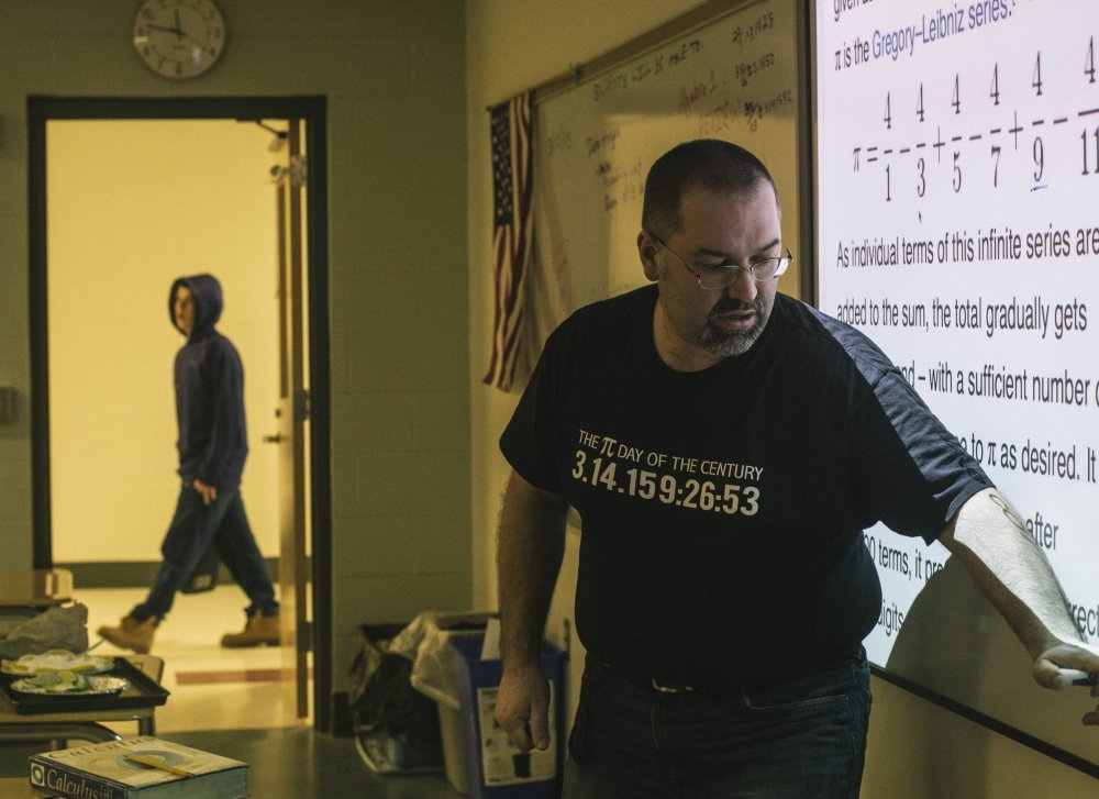 "Biddeford High School math teacher Jon Jacques instructs his calculus class while wearing a shirt with some of the numbers of pi written out. Jacques does parody songs for Pi Day, and has spoofed Queen's ""Bohemian Rhapsody"" into ""Pi-Rational Rhapsody."""