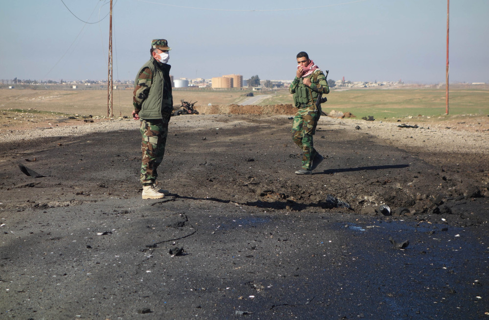In this undated photo made avaialble Saturday by the Kurdistan Region Security Council (KRSC), Kurdish soldiers survey the site of a bomb attack on a road between Mosul, Iraq, and the Syrian border in northern Iraq.