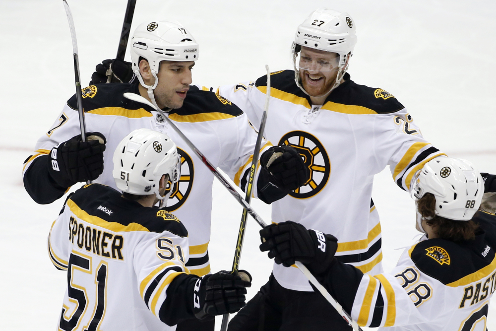Milan Lucic, 17, of the Bruins celebrates his first-period goal with teammates Saturday in Pittsburgh. The Bruins added an empty-net goal in the final minute for a 2-0 win, their fifth straight.