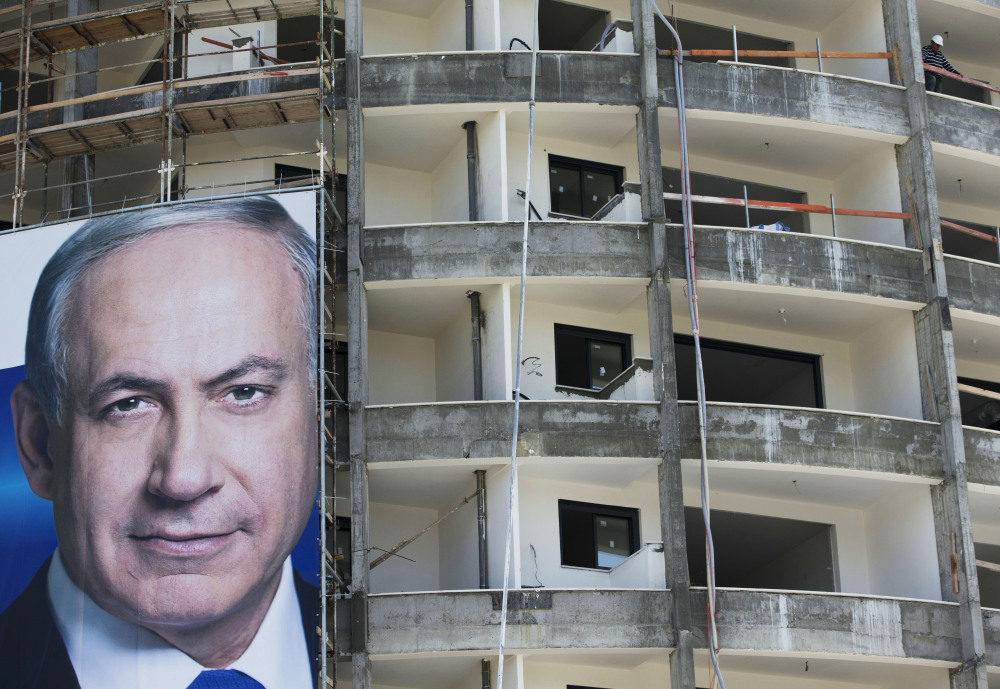 Prime Minister Benjamin Netanyahu's campaign poster hangs at an Israel construction site in the run-up to Tuesday's parliamentary elections.