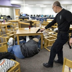 """Independence, Mo., police hold an active-shooter training session for the staff of Pioneer Ridge Middle School. In their first scenario, the staff was told to just take cover. This allowed the gunman, played by Sgt. Chris Summers, to """"kill"""" many victims."""