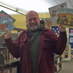 Bus driver Donald Sanders holds a selection of children's books that are getting a lot of mileage as part of the Bus Book Bags program in SAD 75.