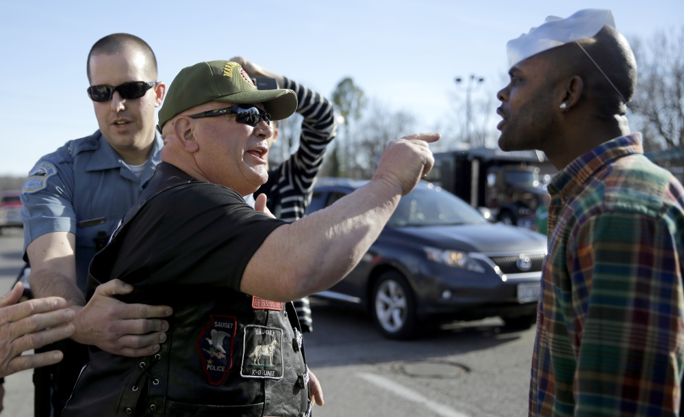 A pro-police protester, left, and counter-protester yell at each other outside the Ferguson police station Sunday in Ferguson, Mo. About 100 people came out to show their support for law enforcement.