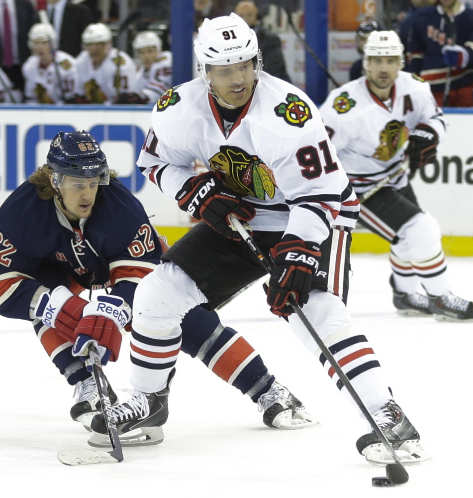 Brad Richards of the Blackhawks controls the puck while being hounded by New York's Carl Hagelin on Wednesday night in New York. Richards scored in Chicago's 1-0 win.