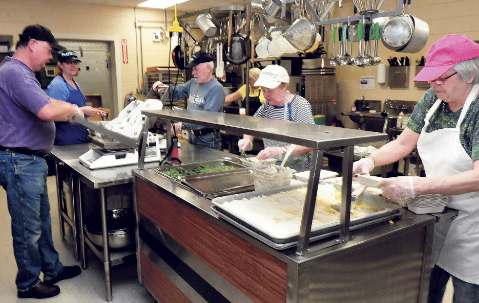 Volunteers at the Muskie Center in Waterville prepare dinners for the Meals on Wheels program Wednesday. From left are John Veilleux, Victoria Veilleux, Vaughn Tuttle, Rita Tuttle and Cheryl Gulliver.