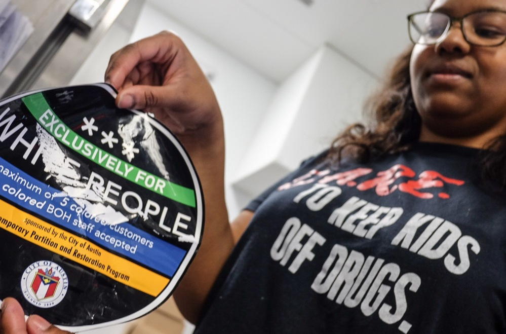 April Jensen, an employee at Sugar Mama's, holds a sticker found on the front of the store in Austin, Texas, on Wednesday.