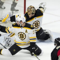Ottawa Senators left wing Milan Michalek scores against Boston Bruins center Patrice Bergeron and goalie Tuukka Rask during the first period of Thursday night's game in Ottawa. The Senators went on to win, 6-4.