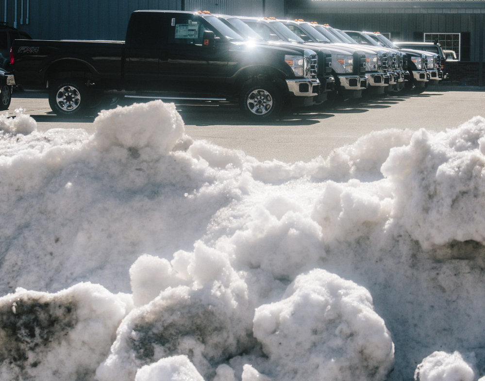 """Trucks and snow vie for space Thursday at Arundel Ford. The president of the Maine Automobile Dealers Association said the winter had a """"disruptive effect on sales volumes."""""""