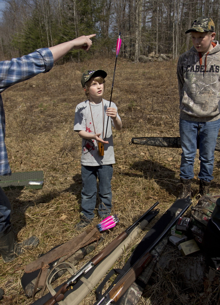 A youngster learns to balance an arrow at a hunting camp last year in Casco. The sponsorship of a new bill to designate a Youth Bear Hunting Day raises a question of conflict of interest, a reader says.
