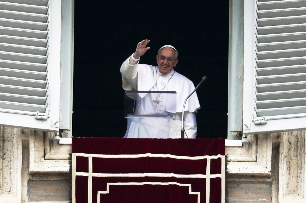 Pope Francis waves as he leads the Angelus prayer from the window of the Apostolic Palace in St. Peter's Square at the Vatican on Sunday.