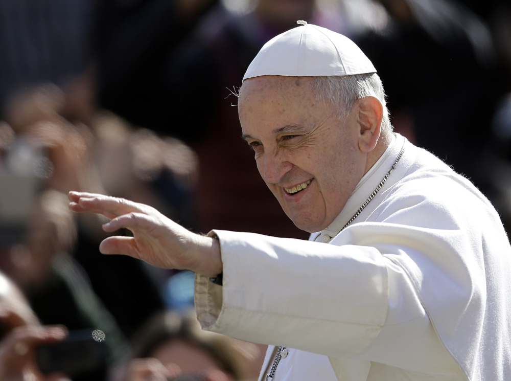 Pope Francis waves to the faithful as he arrives in St. Peter's Square for his weekly general audience Wednesday.