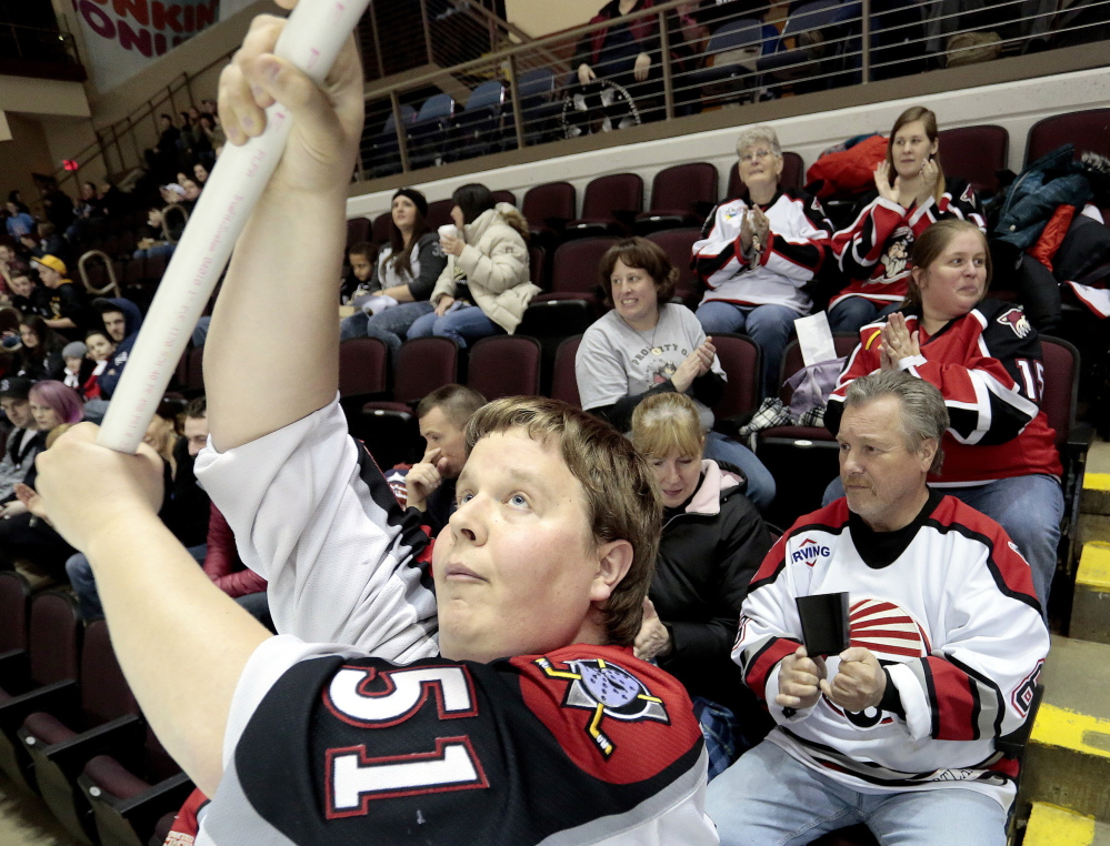 """Andrew Hart of South Portland waves a flag as the Portland Pirates take the ice against the Hershey Bears at Cross Insurance Arena on Friday night. Hart calls the Pirates' new affiliation with the Florida Panthers """"a very welcome change."""""""