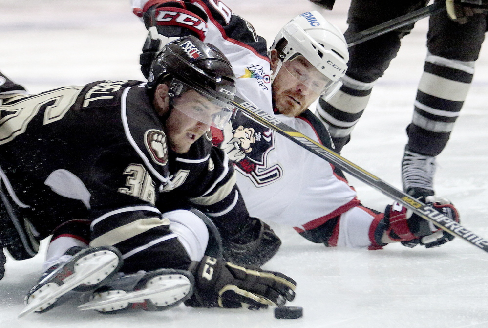 Garrett Mitchell of the Hershey Bears tries to keep the puck away from an incoming Alexandre Bolduc of the Portland Pirates during the first period of Hershey's 3-2 overtime victory at Cross Insurance Arena on Friday night.