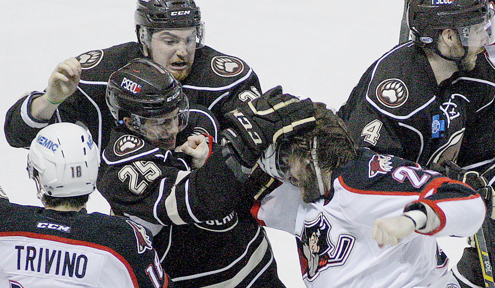 Hershey's Connor Carrick tears at the helmet of the Pirates' Eric Selleck during a second-period fight Friday night, while the Bears' Liam O'Brien, top, tries to intervene.