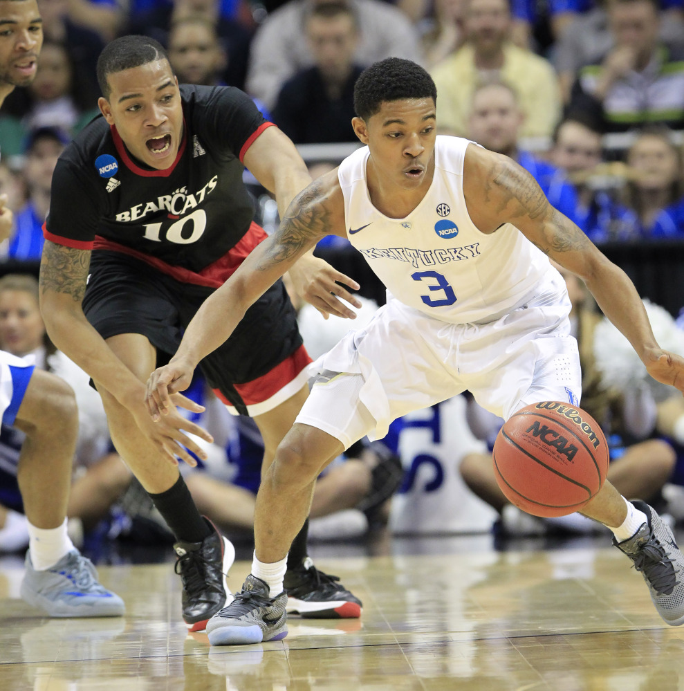 Cincinnati guard Troy Caupain and Kentucky guard Tyler Ulis watch the ball after Caupain knocked it loose during the first half of an NCAA tournament college basketball game in Louisville, Ky., Saturday.