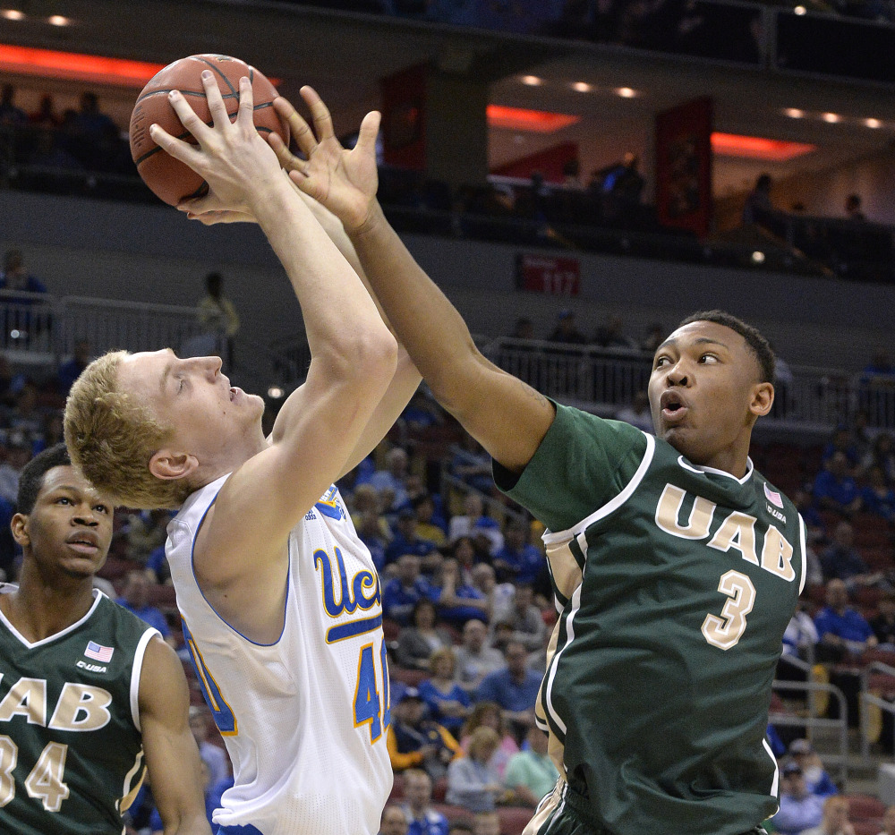UAB's Chris Cokley, right, attempts to tip the ball away from UCLA's Thomas Welsh in the first half of Saturday's NCAA tournament game at Louisville, Ky. The Bruins won 92-75 to reach the Sweet 16.