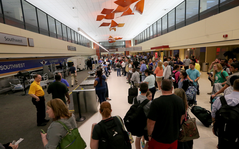 Long lines of fliers await word of their departures in the ticketing area of Louis Armstrong International Airport after a machete-wielding man was shot by a TSA employee on Concourse B on Friday.