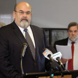 Gardiner Mayor Thom Harnett looks on March 18 as Augusta Mayor Dave Rollins speaks at the Mayors' Coalition on Jobs and Economic Development news conference. Service-center communities need to show state officials that they're prepared to develop more efficient ways to provide services.