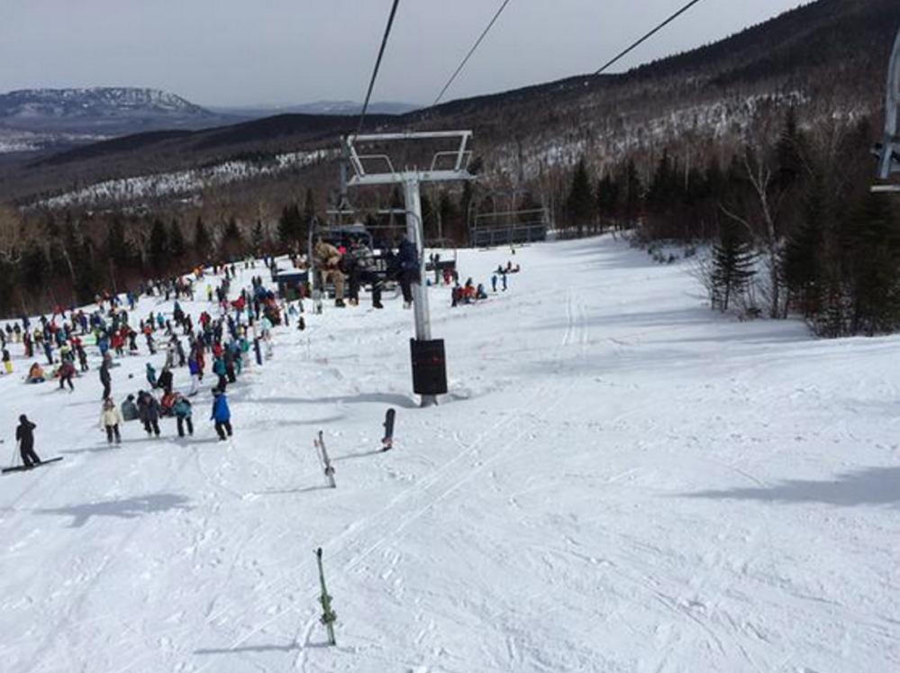 Skiers gather near the Sugarloaf ski lift that malfunctioned Saturday. The resort said Wednesday that engineers identified a design flaw in one of the emergency braking systems.