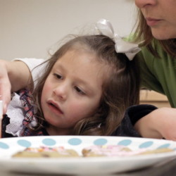 Zoey Houston, 3, makes cookies with occupational therapist Amy Smith at the New England Rehabilitation Hospital in Portland. Smith is trying to break Zoey's habit of using only her right hand.